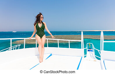 Young woman in black-green swimsuit standing on the deck of...