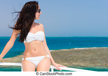 Young brunette in swimsuit standing on the yacht at a sunny...