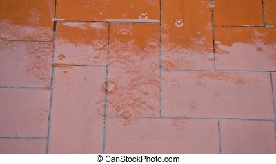 raindrops falling red floor splashes heavy rain with water stream and bubbles