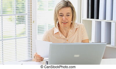 Office Work - Middle Age Female Bookkeeper Paying Bills With...