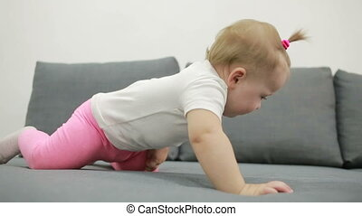 little girl playing on the couch at the living room - baby...