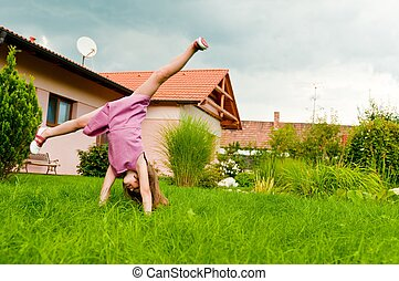 Cartwheel -fun on garden - Small girl making cartwheel on...