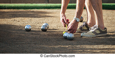 Petanque game,measuring the distance, deciding who's the...