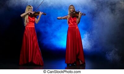 Two girls blonde to play the fiddle. Smoky background with...