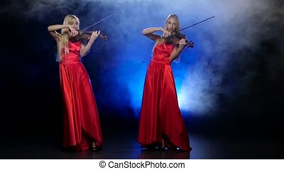 Two girls blonde to play the violin. Smoky background with...