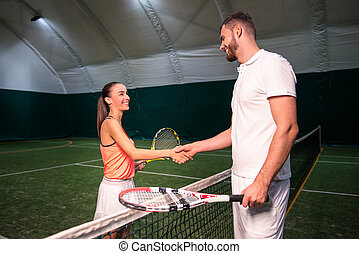 Positive tennis players shaking hands