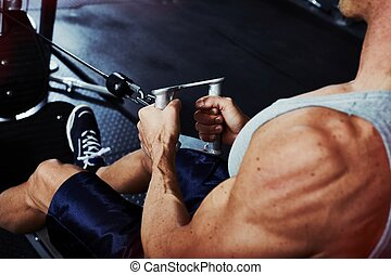 Gym workout - Strong young man exercising in gym. Sport