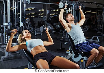 Dumbbell bench press workout - Strong young athletic couple...