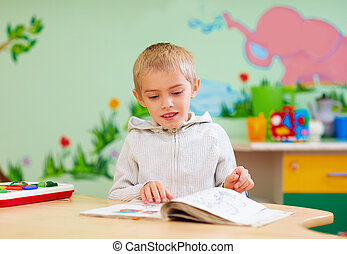 cute boy, kid with special needs looking at a book, in...