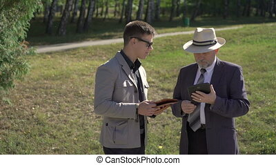 Young and old businessmen speaking and working with tablet on the street. 4K