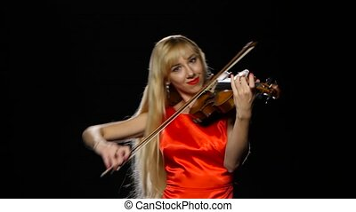 Girl plays the fiddle. Studio. Close-up. Black background -...
