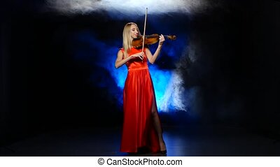 Girl in a red dress playing the fiddle. Studio. Smoke