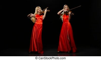 Two women playing the viola. Studio. Black background - Two...