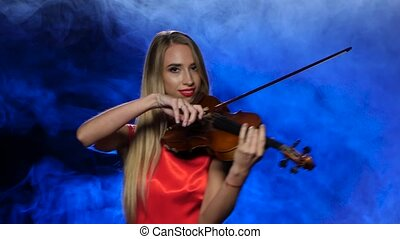 Girl professional fiddler playing the viola. Studio. Smoke -...