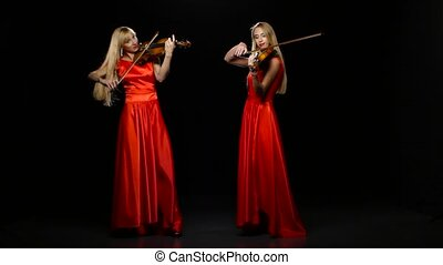Two women playing the fiddle. Studio. Black background - Two...