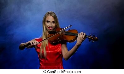 Girl blonde plays the violin professional. Smoky background....