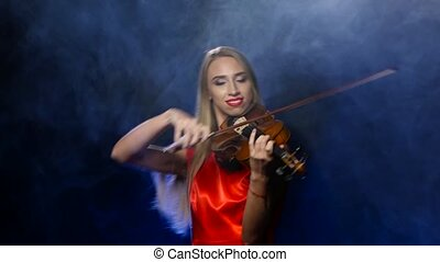 Woman in a red dress playing the fiddle. Studio. Smoke