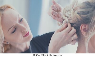 Hair accessory. Wedding stylist helps to collect the bride....