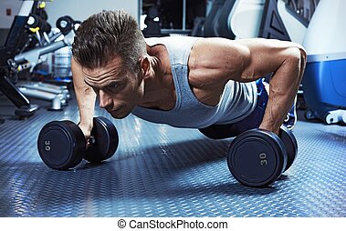 push-up with dumbbells - Strong young man exercising push-up...