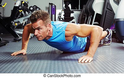 push-up - Strong young man exercising push-up in gym. Sport