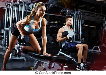 bent over dumbbell workout - Strong young athletic couple...