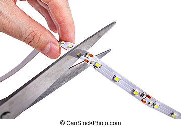 Close-up of hands hold scissors that are cutting LED strip....