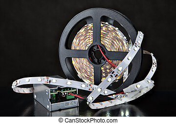 Shining LED Light Strip, and voltage adapter, on black...