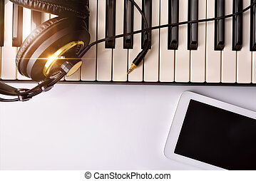 Electronic piano with headphones and tablet for musical...