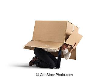 Afraid businessman is hiding under a cardboard