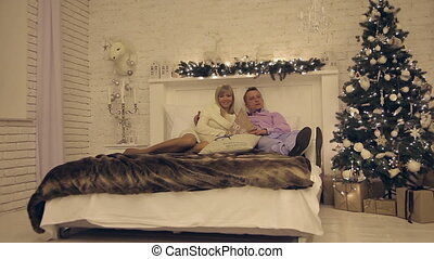 Happy young couple on New Year's night lying on the sofa