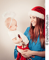 Mother wearing santa hat holding baby