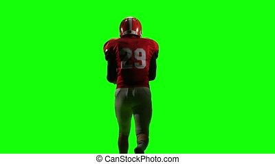 Athlete runs in a red helmet and protective gear with the ball in his hands. Green screen, back view