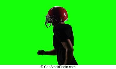 Sportsman running on the field in a helmet and gloves. green...