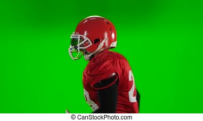 Football player running red uniform and helmet. Green...