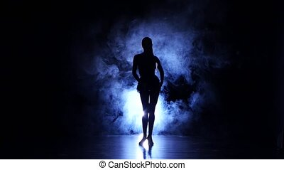 Graceful girl dancing in studio, silhouette. Dark background, blue backlight