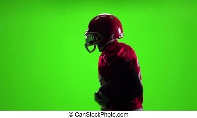 Athlete in red uniform with a ball. Slow motion. Side view....
