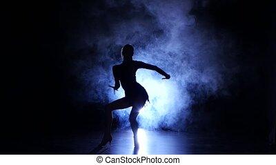 Girl dancing movements of salsa, rumba, silhouette. Dark...