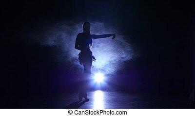 Girl dancing movements of salsa, rumba, silhouette. Dark background, blue backlight