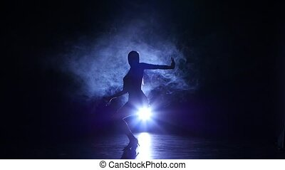 Dancing girl rumba in studio, silhouette. Blue backlight -...