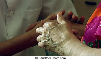 Taking care - Nurse and senior citizen holding hands