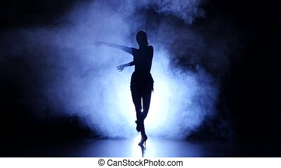Woman dancing samba in studio, silhouette. Dark background, blue backlight