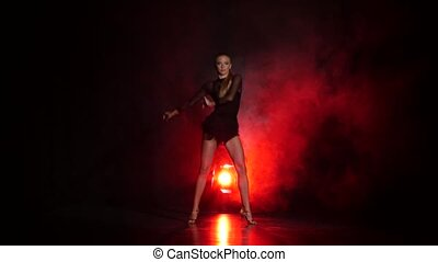Dancer in studio with red illumination on a dark background...