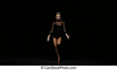 Girl dancing samba in a studio on a dark background -...