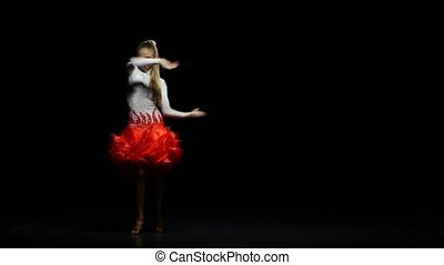 Woman dancing rumba in a studio on a dark background - Woman...