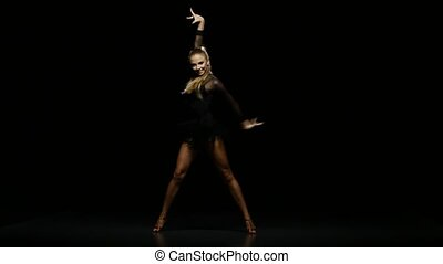 Girl dancing latin in a studio on a dark background - Woman...