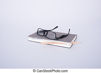 notebook with glasses and pen on the blackground. - notebook...