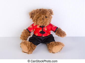 toy or teddy bear with chinese red shirt on background. -...