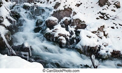 Water in frozen stream. Snowy river in forest in the winter....