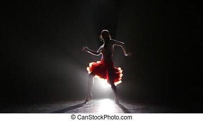 Beautiful girl dancing rumba in the studio on a dark...