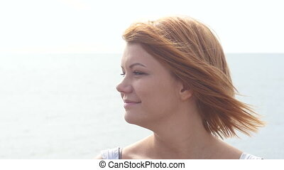 Close up portrait of beautiful young redhead woman on the...